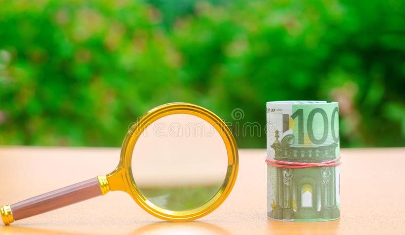 Euro banknotes and magnifying glass. The concept of finding sources of investment and sponsors. Find a money. Charitable funds. royalty free stock photography