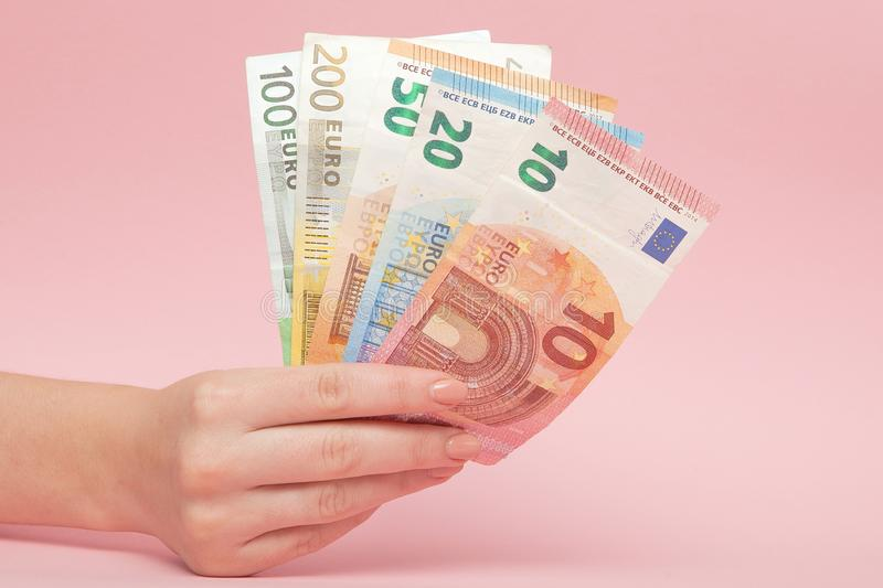 Euro banknotes money in female hands on pink background. Business Concept and Instagram royalty free stock photography