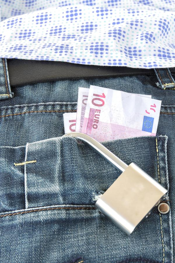 Euro banknotes in a pocket locked with a padlock. Euro banknotes protruding from a pocket locked with a padlock royalty free stock image