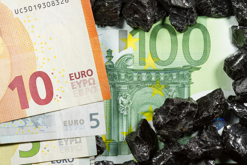 Euro banknotes on raw coal nuggets, bills on coal, power of money and ore royalty free stock photo