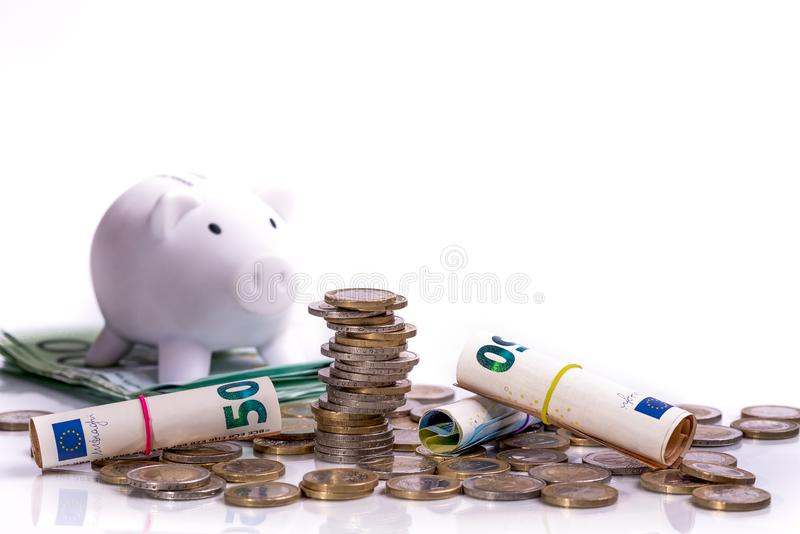 Euro banknotes rolled up and euro coins at different positions White coin piggy bank stock photo