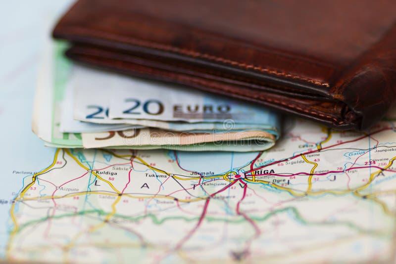 Euro billets de banque à l'intérieur de portefeuille sur une carte géographique de Riga photographie stock libre de droits