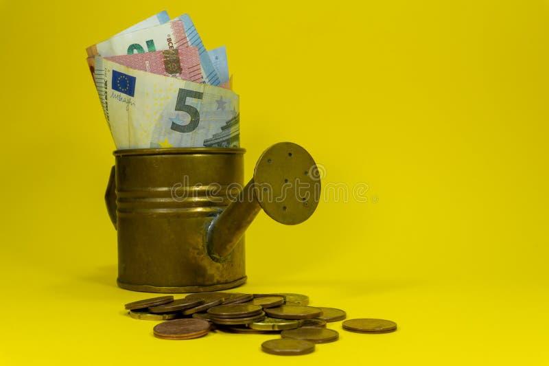 Euro billets de banque dans une boîte d'arrosage de cuivre photos stock