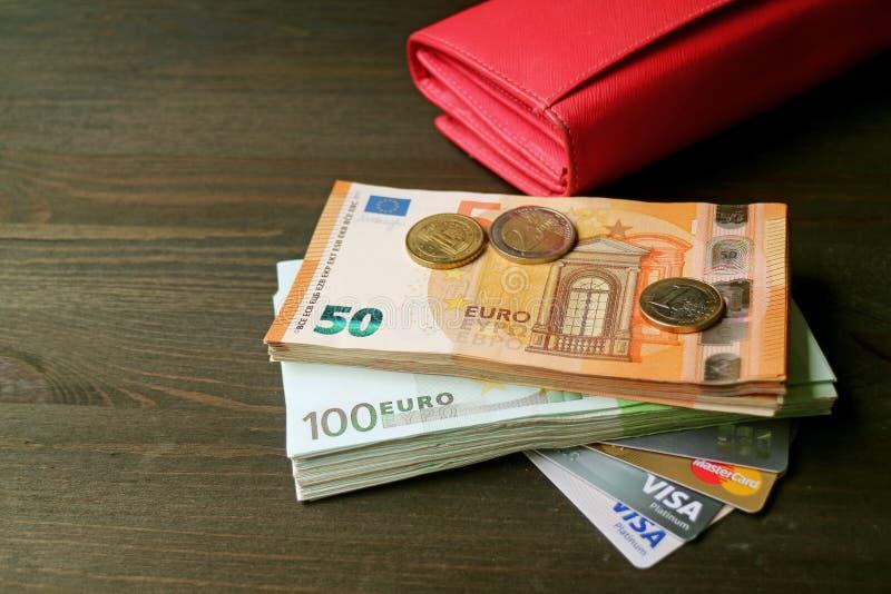Euro billets de banque et pièces de monnaie avec de diverses cartes de crédit et un portefeuille rouge à l'arrière-plan image libre de droits