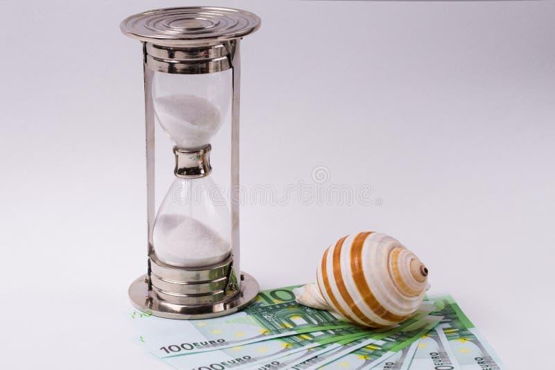 EURO billets de banque, sablier et coquillage sur le fond blanc Concept - heure de voyager photo stock