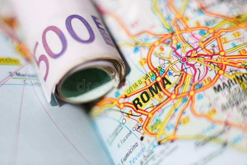Euro billets de banque sur une carte géographique de Roma images stock