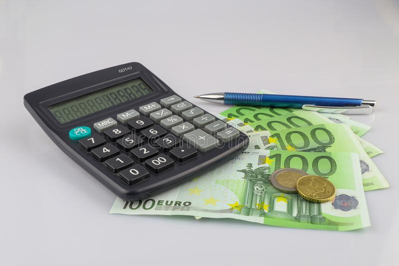 100 euro bills euro banknotes and coins money with calculator and pen. European Union Currency.  Isolated background stock image