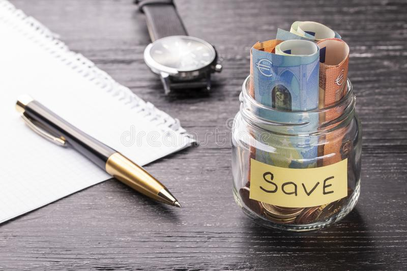 Saving money in a glass jar royalty free stock photo