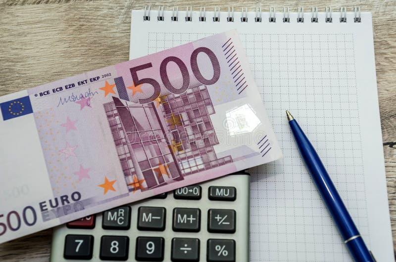 500 euro, calculadora, cuaderno y primer de la pluma fotografía de archivo