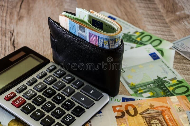 Euro, calculator en portefeuille met geld op houten achtergrond royalty-vrije stock afbeeldingen