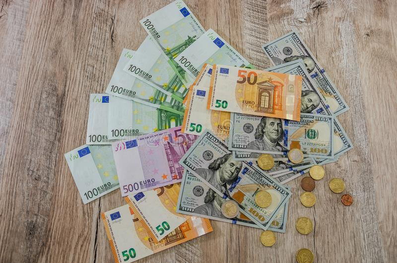 Euro, dollars, cents spread out on a wooden background royalty free stock photography