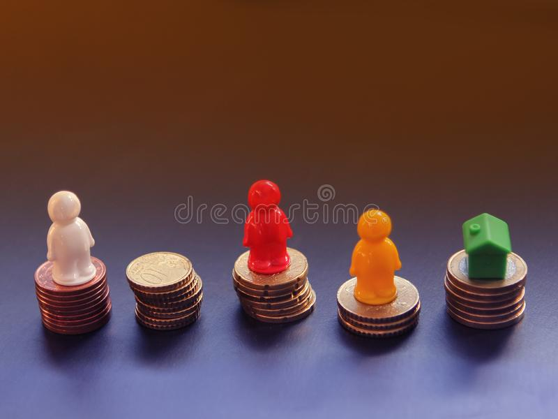 Euro cent coins are stacked on a dark colored background. On one pile stands a small house figure. Concept business, real estate, stock images