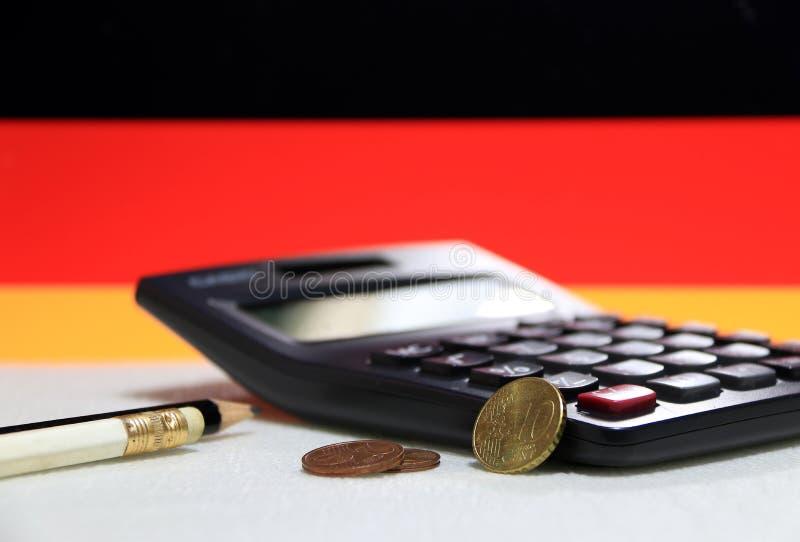 Euro cent de Dix Allemagne sur l'inverse et la pièce de monnaie deux de l'euro cent deux sur le plancher blanc avec la calculatri photos stock