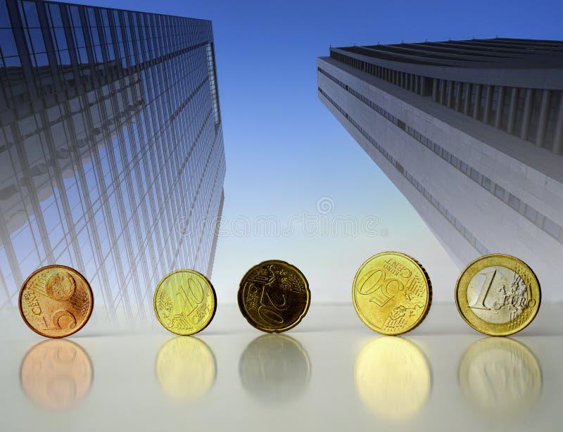 Euro cents debout de pièces de monnaie sur le fond d'affaires de gratte-ciel photographie stock