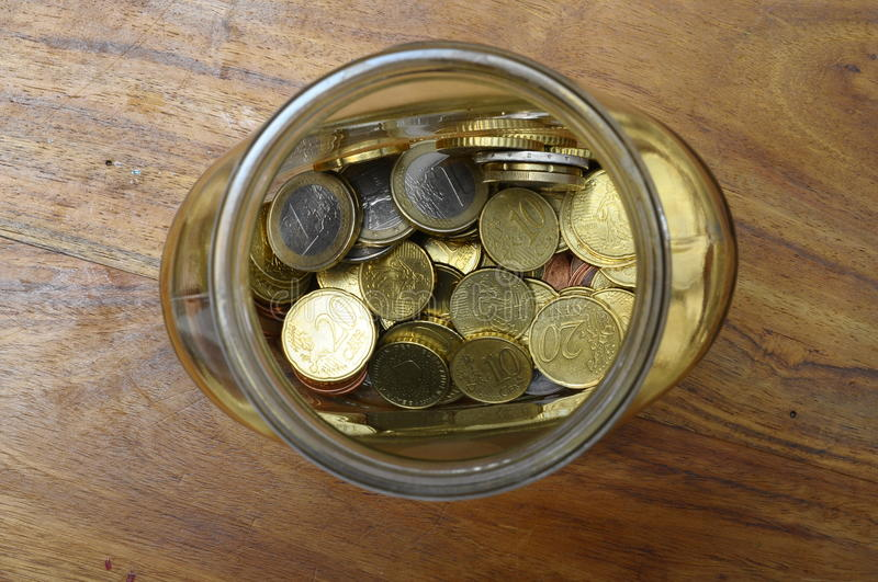 Euro cents in a glass jar. As piggy bank on wooden table stock image