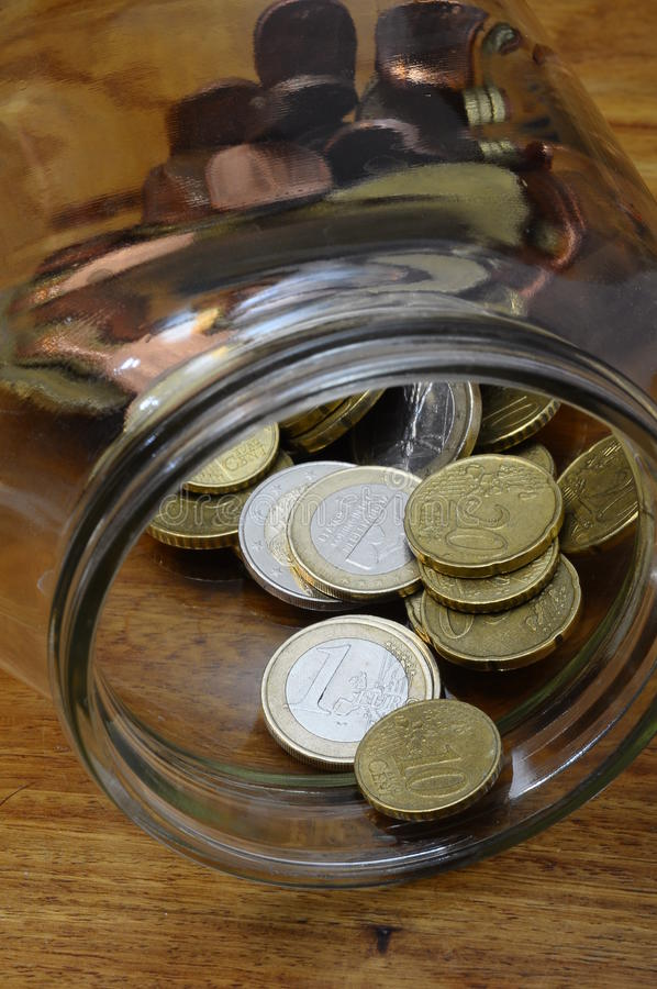 Euro cents in a glass jar. As piggy bank on wooden table stock photos