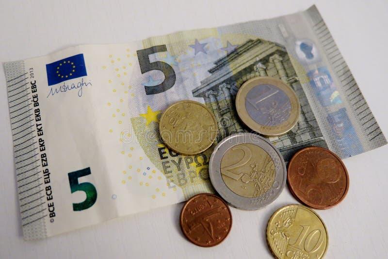 Euro cinco e uma moeda de um centavo em um close-up branco do fundo fotos de stock royalty free