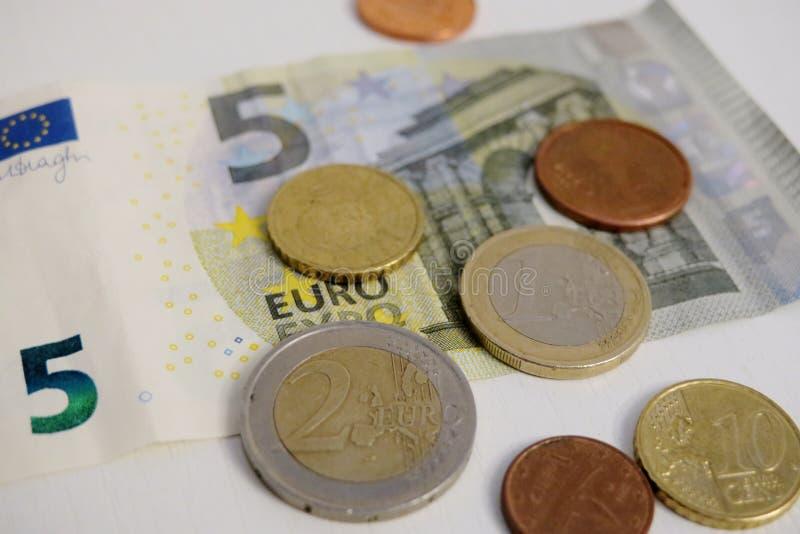 Euro cinco y un penique en un primer blanco del fondo fotografía de archivo libre de regalías