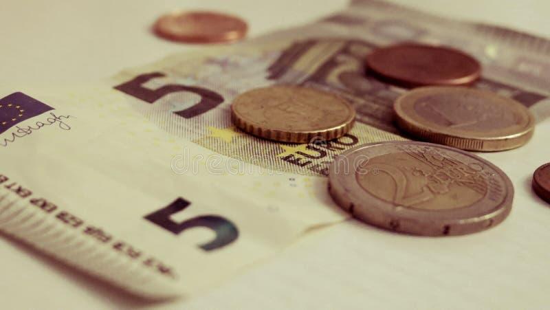Euro cinco y un penique en un primer blanco del fondo fotos de archivo