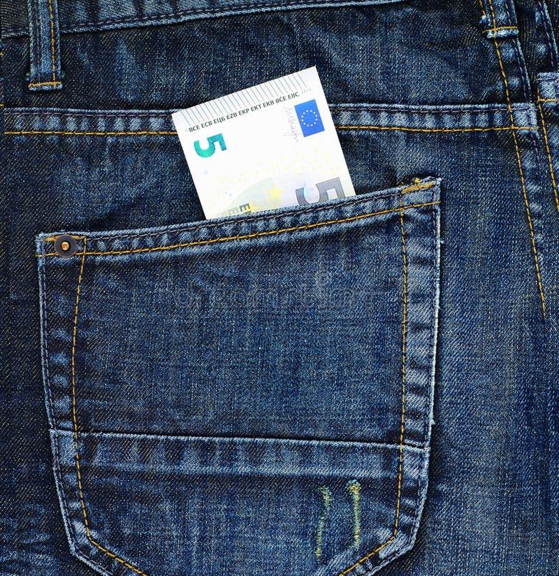 Euro cinq dans une poche arrière de jeans image stock
