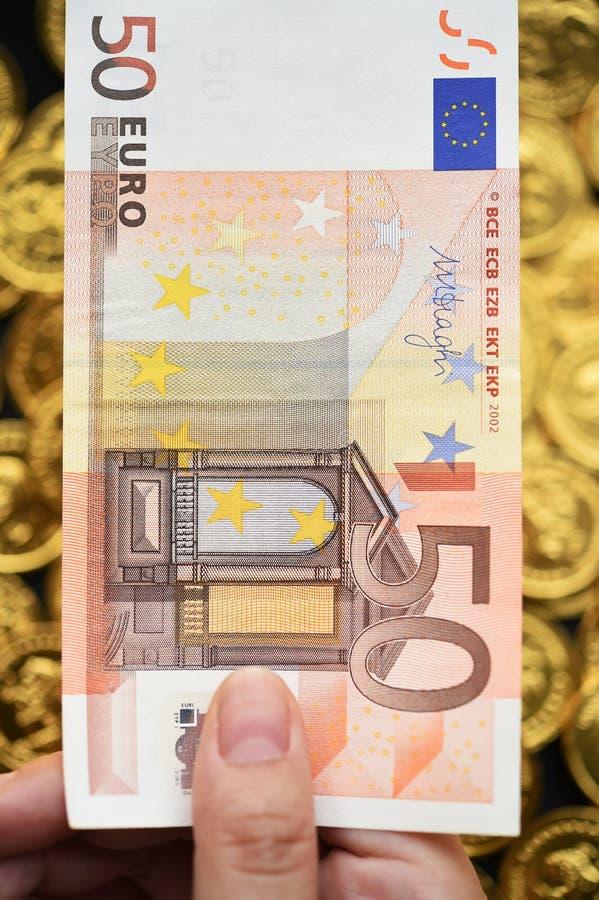 Euro cinquante en main avec des pièces d'or photographie stock libre de droits