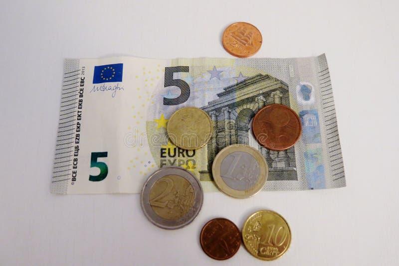 Euro cinque e un penny su un primo piano bianco del fondo fotografie stock libere da diritti