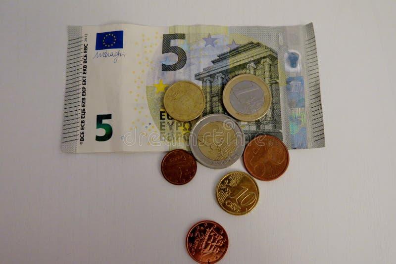 Euro cinque e un penny su un primo piano bianco del fondo fotografia stock libera da diritti