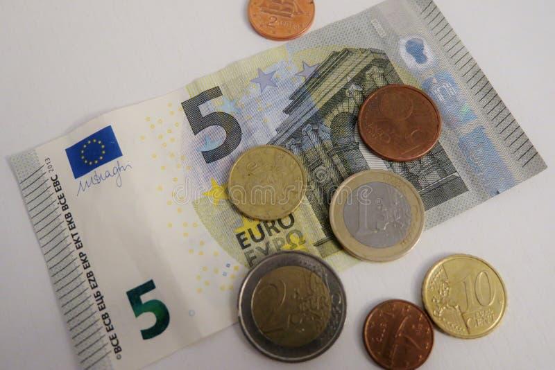 Euro cinque e un penny su un primo piano bianco del fondo immagini stock
