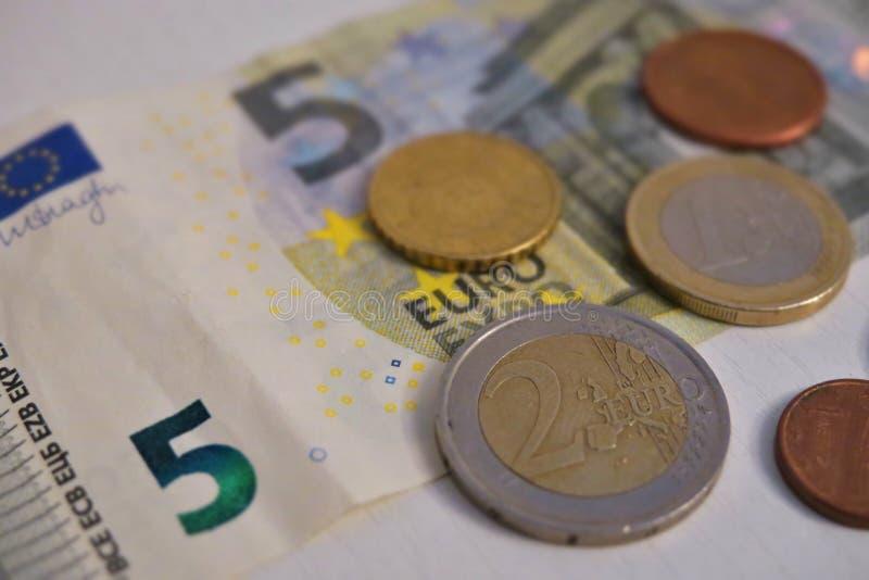 Euro cinque e un penny su un primo piano bianco del fondo immagine stock libera da diritti