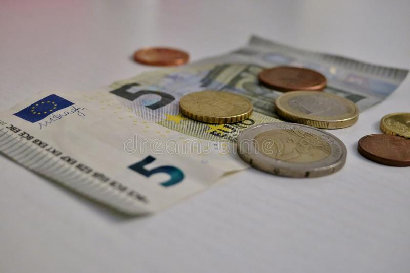Euro cinque e un penny su un primo piano bianco del fondo immagine stock