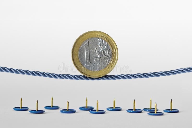Euro coin balancing on rope over push pins - Concept of euro currency risk royalty free stock image