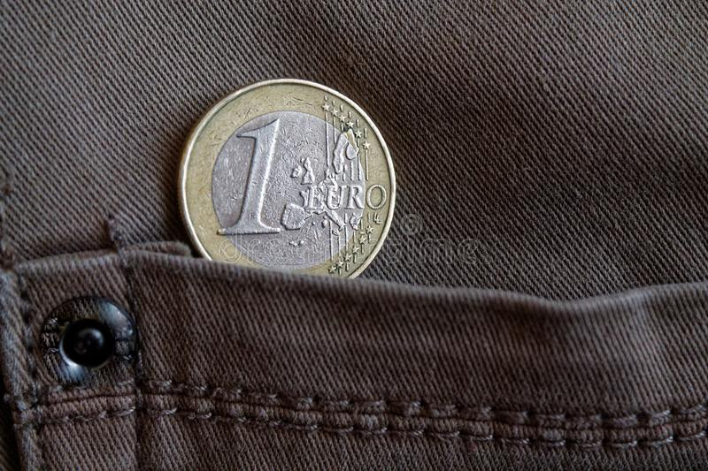 Euro coin with a denomination of 1 euro in the pocket of brown denim jeans stock photography