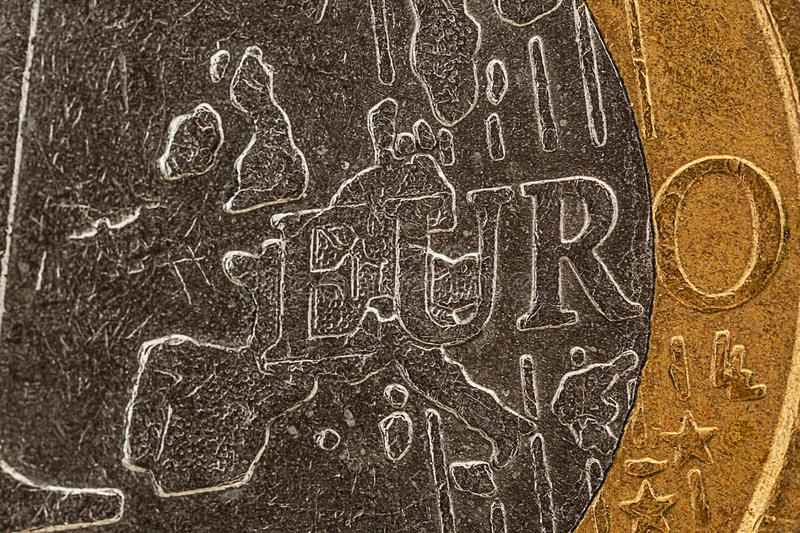 Euro coin extreme close-up. Only the word EURO and the map of Europe are visible, silver and golden colored metal, copper-nickel alloy and the `golden` brass stock photos