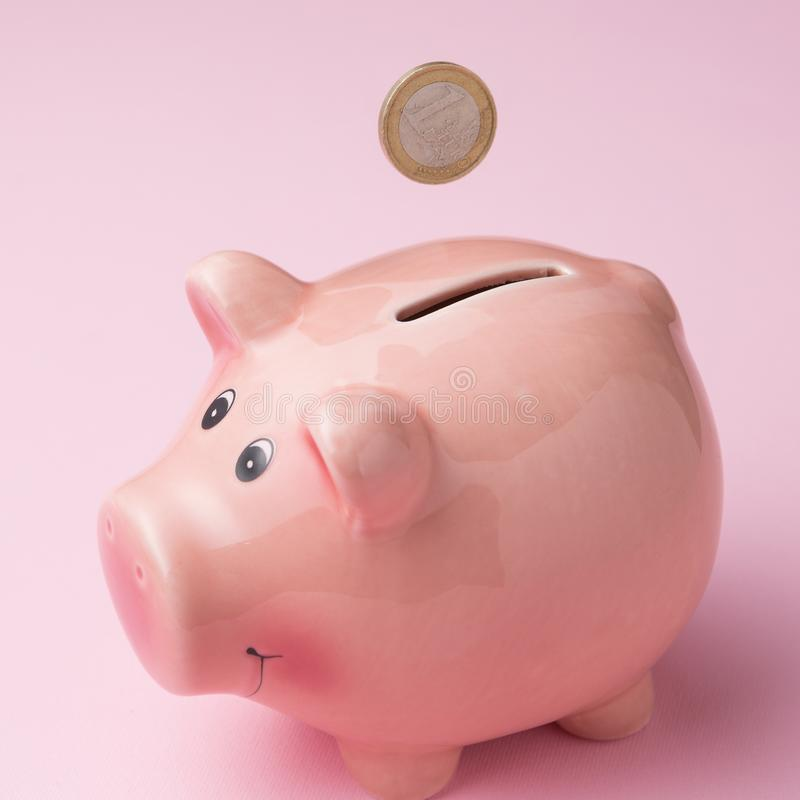 Euro coin falling into a piggy bank, close-up, on a pink background, concept of finance stock photography