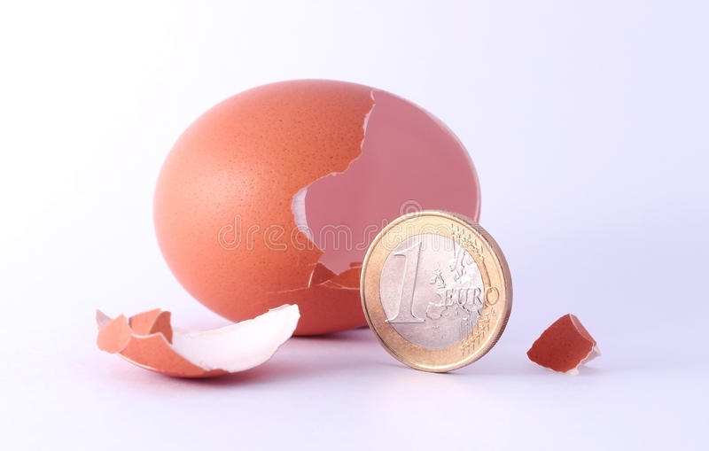 1 euro coin getting out of cracked hatched egg. stock photo