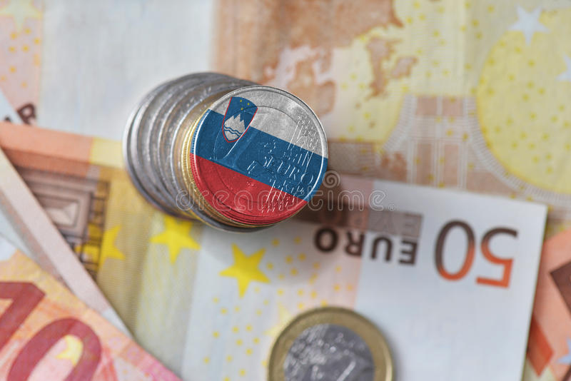 Euro coin with national flag of slovenia on the euro money banknotes background. Finance concept royalty free stock image