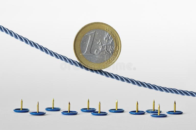 Euro coin on rope over push pins - Concept of downward trend of euro currency and euro currency risk stock images