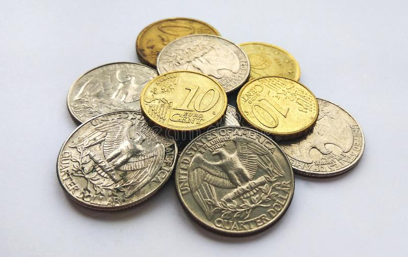 Euro coins and dollar cents on white background. New shiny euro coins and dollar quarter cents on white background stock images