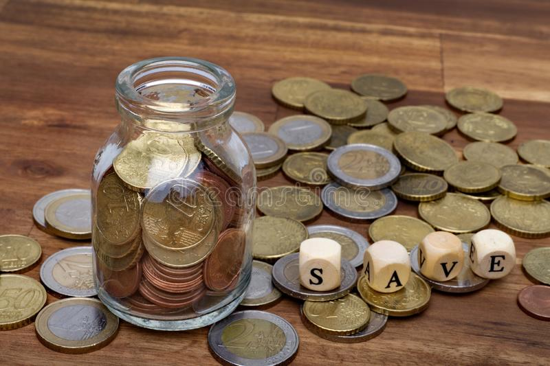 Euro coins in a money box an the table with the word save. On the table royalty free stock image