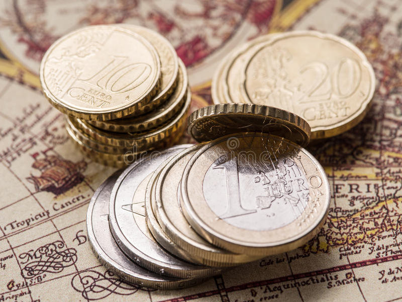 Euro coins over the old world map. Macro picture royalty free stock photos