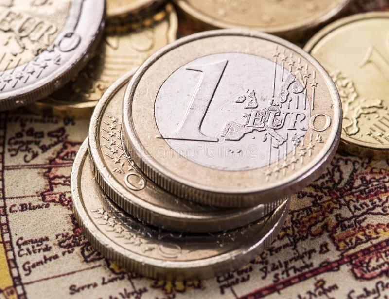 Euro coins over the old world map. Macro picture stock photography