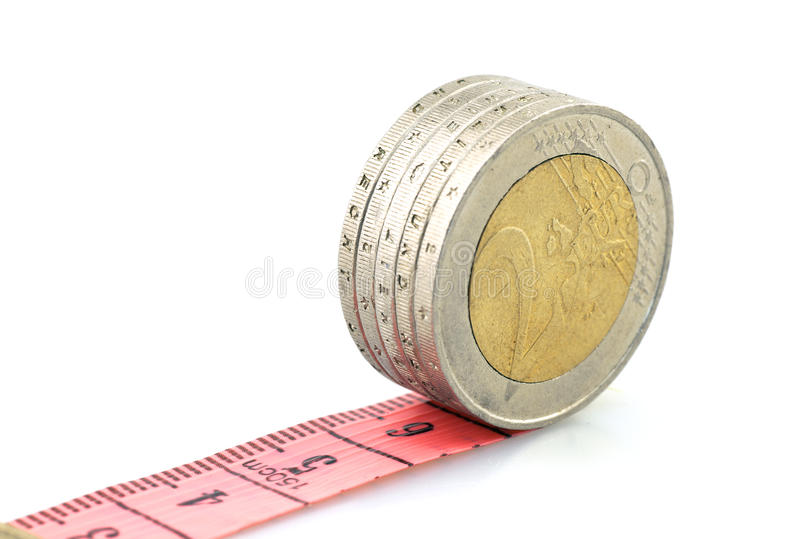 Euro coins running on red ruler. The conceptual measurement of coins on white background indoors,financial concept stock image
