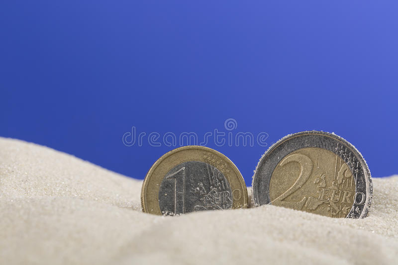 Euro coins in sand on blue background.  stock photo