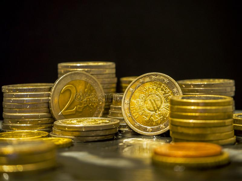 Euro coins on the table. Coin stack with rising chart line, being spotted with scope Stack Euro coins - money stock image