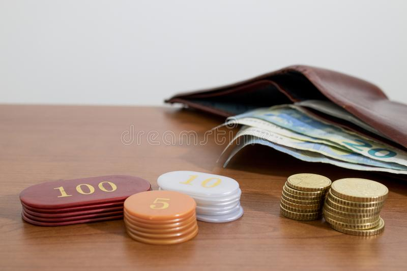 Euro coins a wallet and casino chips on a wood table. Composition stock photography