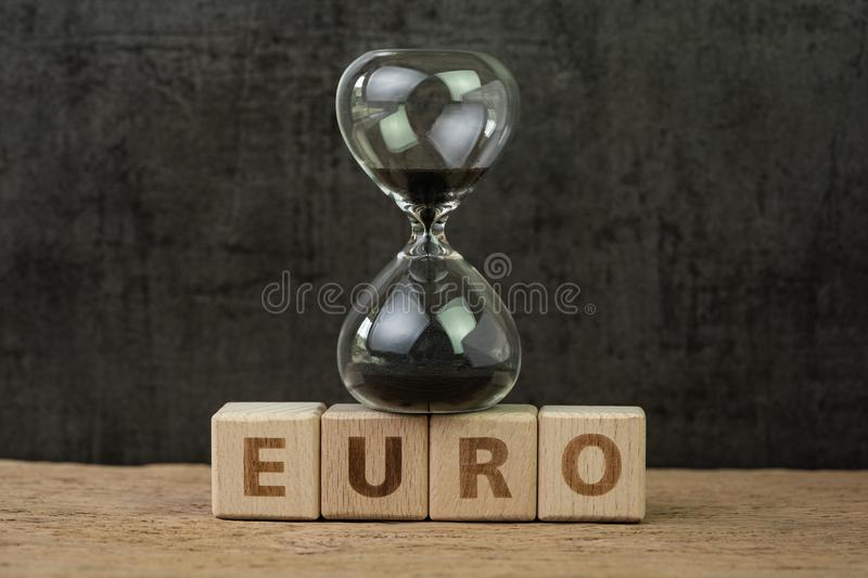 Euro countdown after Brexit referendum to withdraw from Europe, hourglass or sandglass on wooden cube block with alphabet building. The word Euro on wood table stock photography