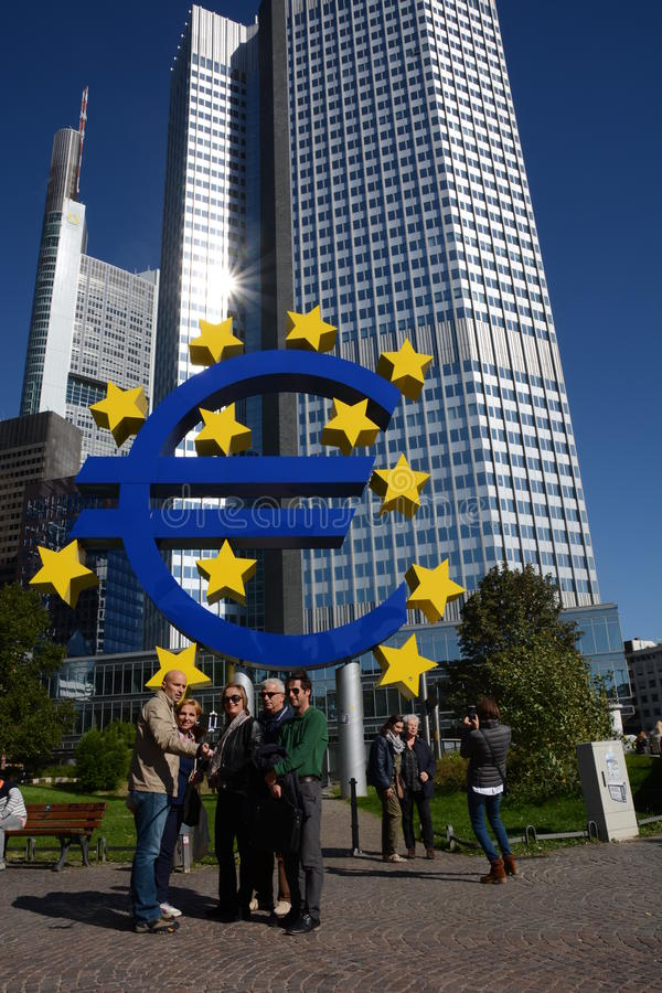 Euro crises. Frankfurt, Germany - October 1, 2015 - Tourist taking pictures in front of Euro Tower with euro sculpture during finance and refugee crises in royalty free stock photo
