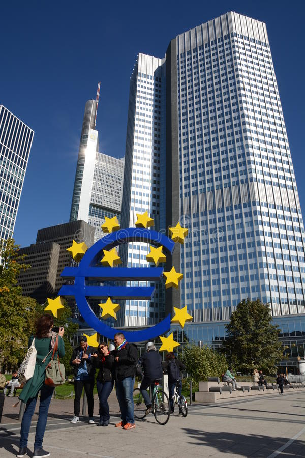 Euro crises. Frankfurt, Germany - October 1, 2015 - Tourist taking pictures in front of Euro Tower with euro sculpture during finance and refugee crises in stock image