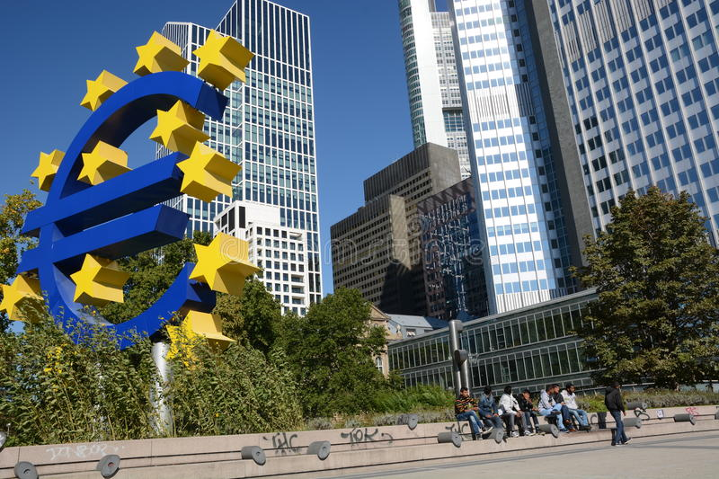 Euro crises. Frankfurt, Germany - October 1, 2015 - Young male refugees hanging around in front of Euro Tower in the financial heart of Europe royalty free stock photo