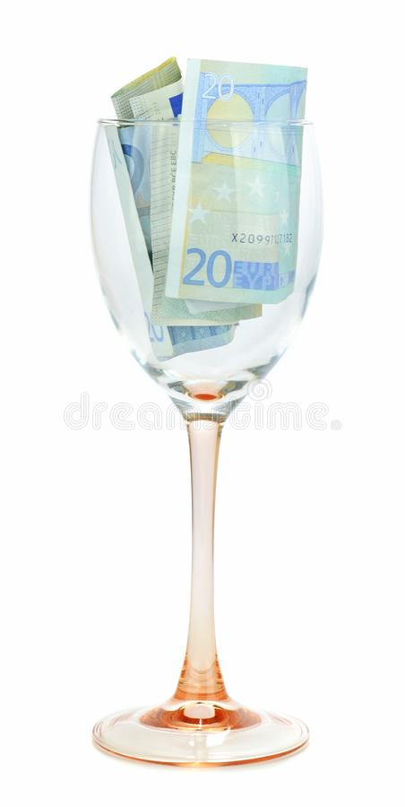 Euro currency banknotes in a wine glass